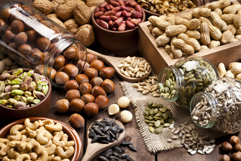 Assortment of nuts on rustic wood table.
