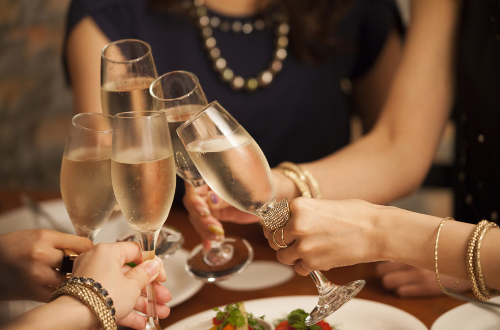 Close up of hands of women toasting with Prosecco