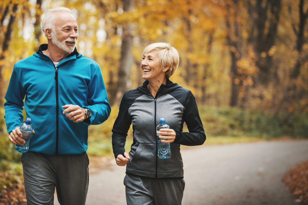 Closeup front view of a senior couple jogging in a forest and having fun. They are running on a winding forest road, laughing and doing their healthy routine. Both holding water bottle.Trees in background have turned orange and yellow and there's a lot of leaves on the side of the road.