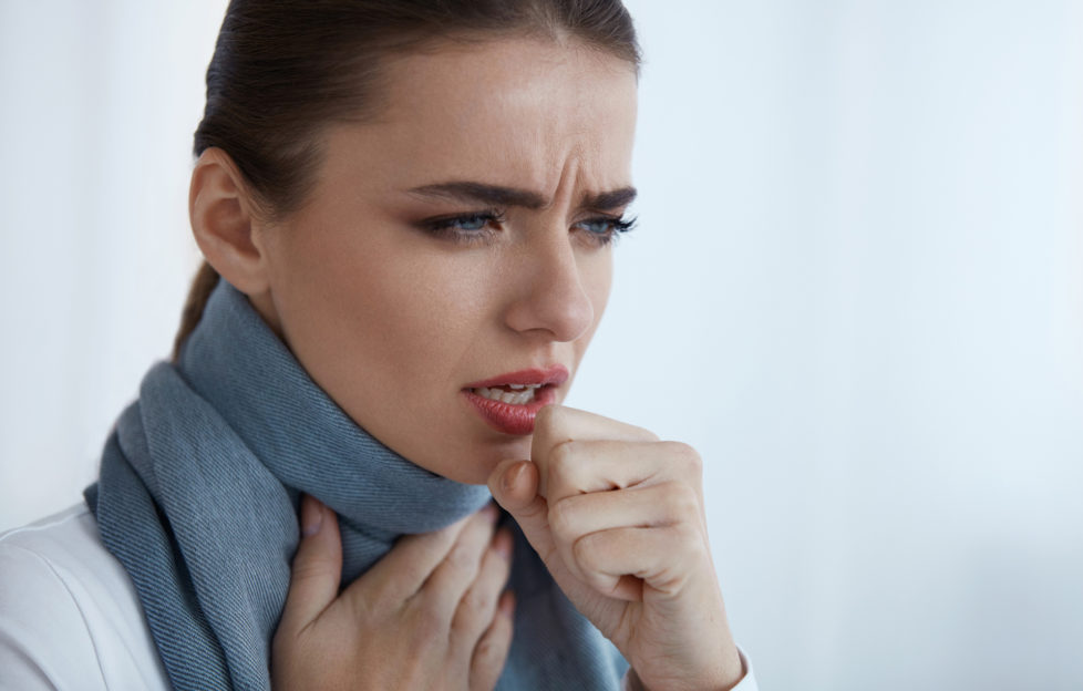 Woman with scarf coughing painfully