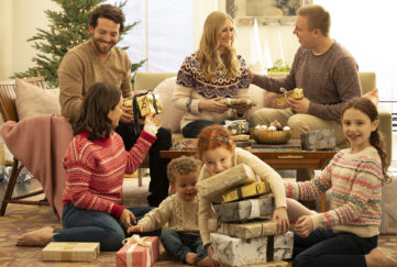 Family opening presents at Christmas in living room