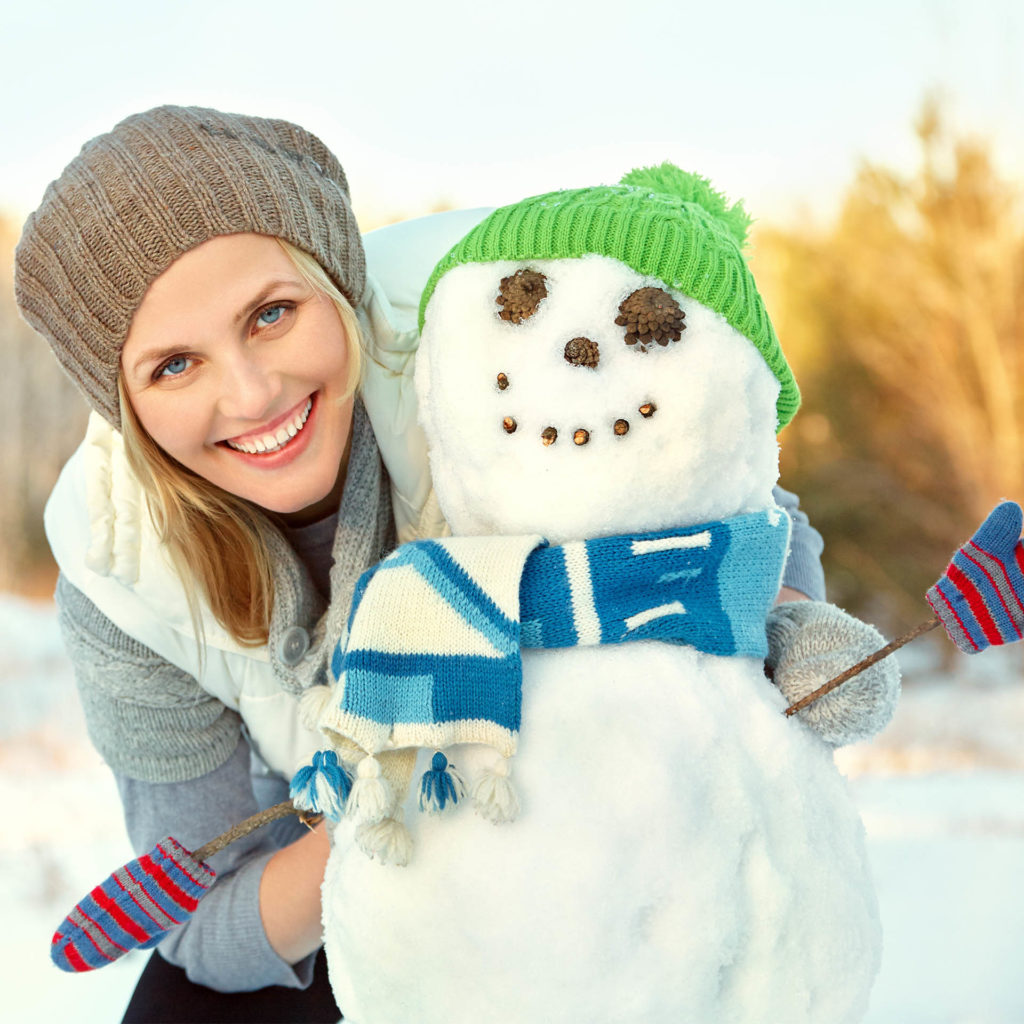 Happy woman with a snowman she has made