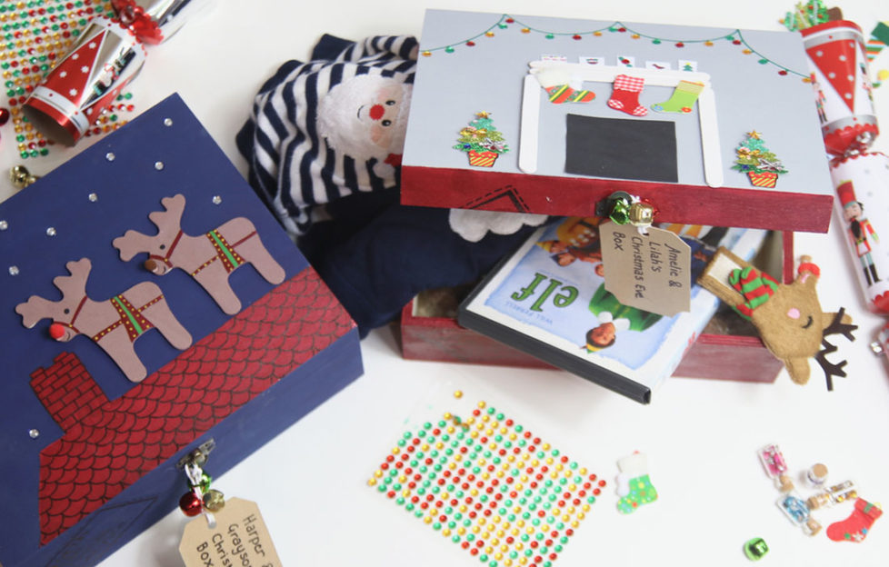 Decorated wooden boxes filled with goodies for Christmas Eve, including Elf DVDand hot water bottle cover