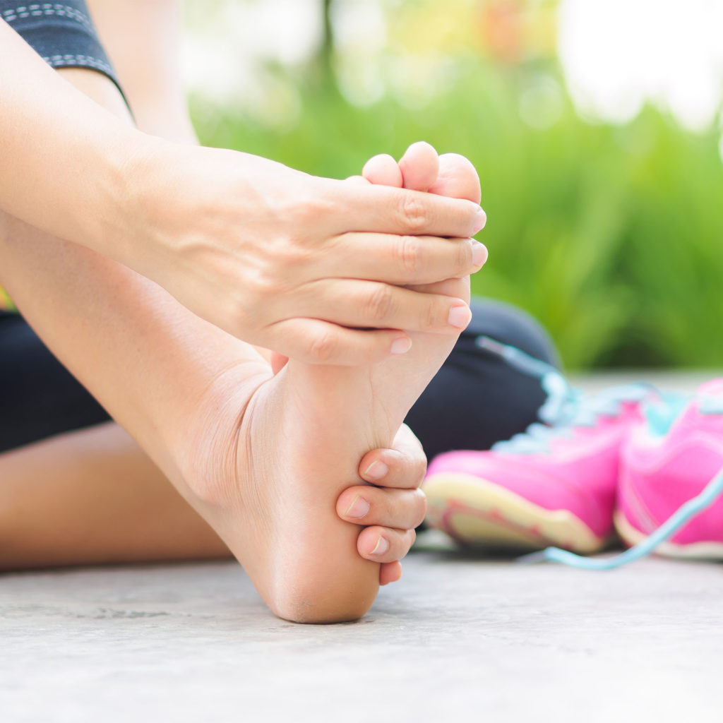 Close up of woman's bare foot, pink trainers behind, she is rubbing her foot to ease cramp