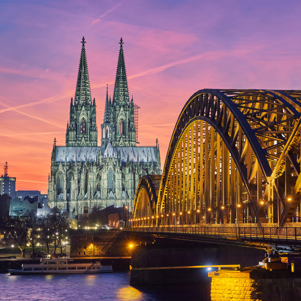 Cologne Cathedral, floodlit in silver, and Hohenzollern Bridge, lit in gold, at sunset with a purple and orange sky