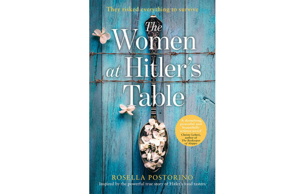 Cover of The Women At Hitler's Table, an old metal spoon lying on a blue wooden table, filled with pale pink flower petals, two strands of barbed wire running horizontally