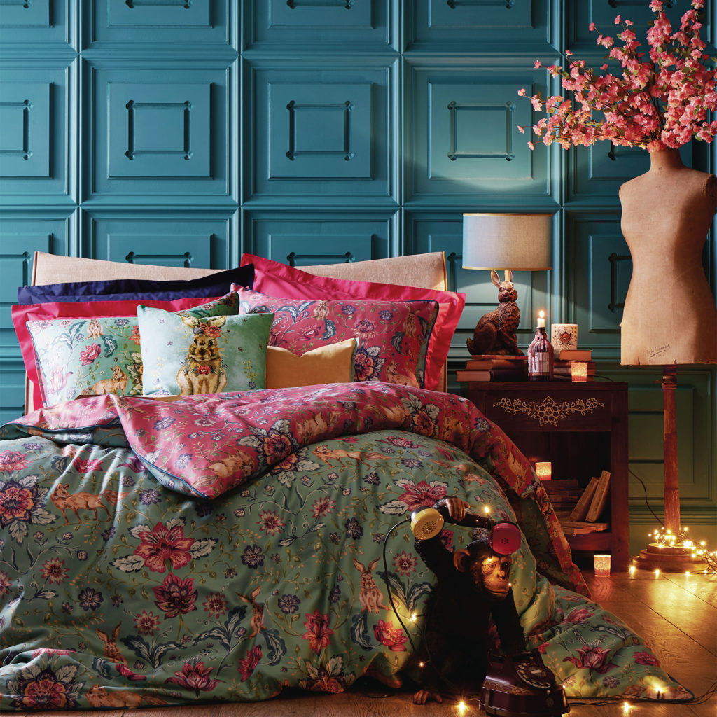 Bed covered with patterned cushions and tapestry style textiles. Wall behind is of square wood panels, painted teal blue. Quirky ornaments such as model chimpanzee answering an old style phone.