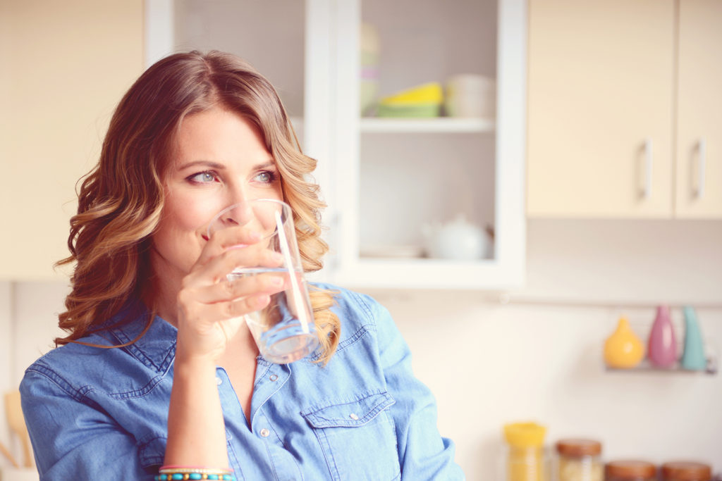 Blonce woman drinking glass of water in kitchen