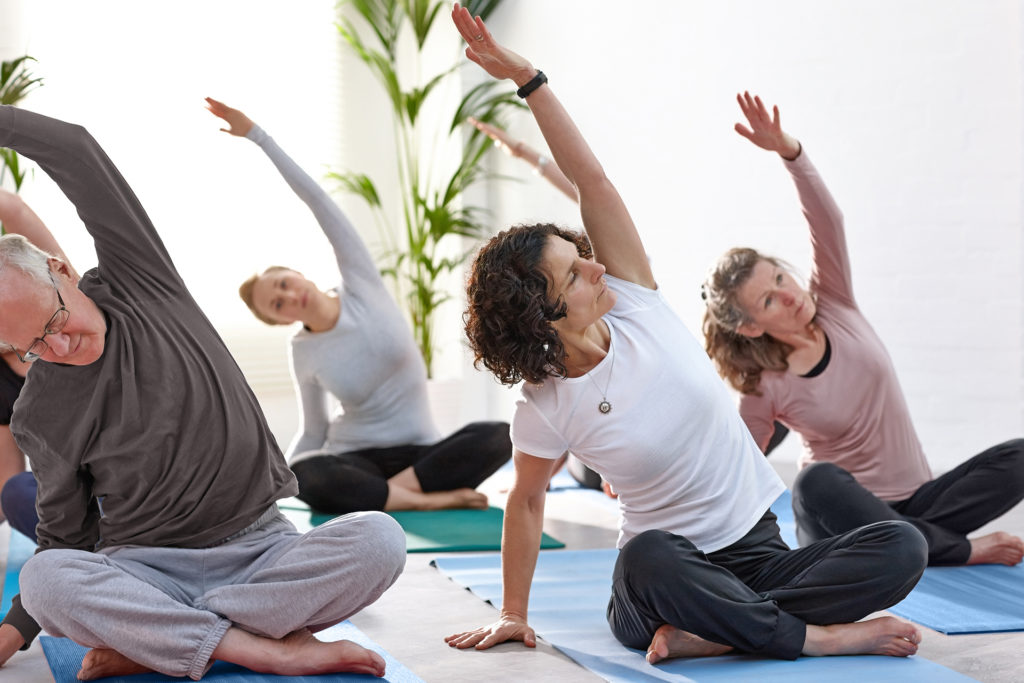 Group of mature people practicing yoga at health club