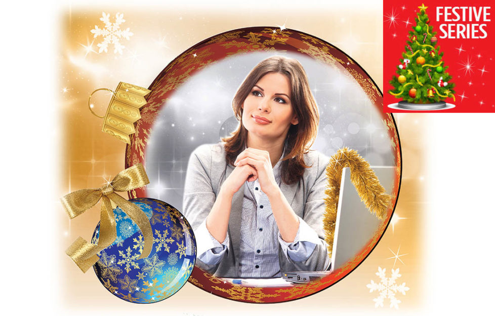 Christmas baubles, one reflecting thoughtful woman sitting at computer