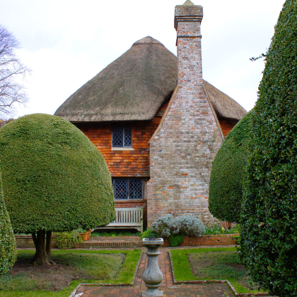 Alfriston Clergy House, National Trust property. Red brick, half timbered, with thatched roof and stone chimney, with neatly trimmed shrubs in foreground