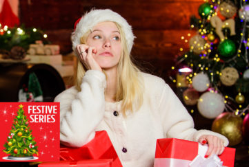 Girl in Santa hat and white jumper, surrounded by wrapped gifts, looking unhappy