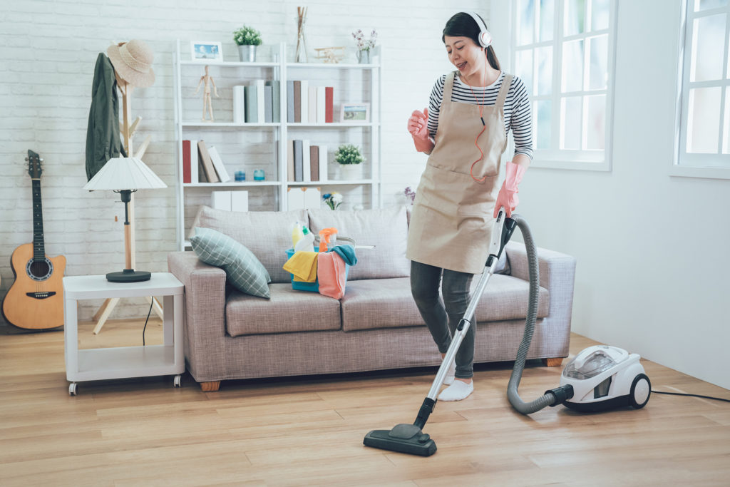Smiling excited young housewife havig fun while cleaning floor with vacuum cleaner. Happy woman doing housework at home enjoy music wearing earphones. lady in apron singing dancing house chores