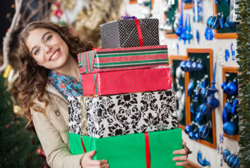Portrait of happy young woman carrying stacked gift boxes in Christmas store.