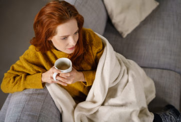 Relaxed young redhead woman enjoying a tea break sitting wrapped in a warm blanket on a comfortable couch staring thoughtfully ahead,