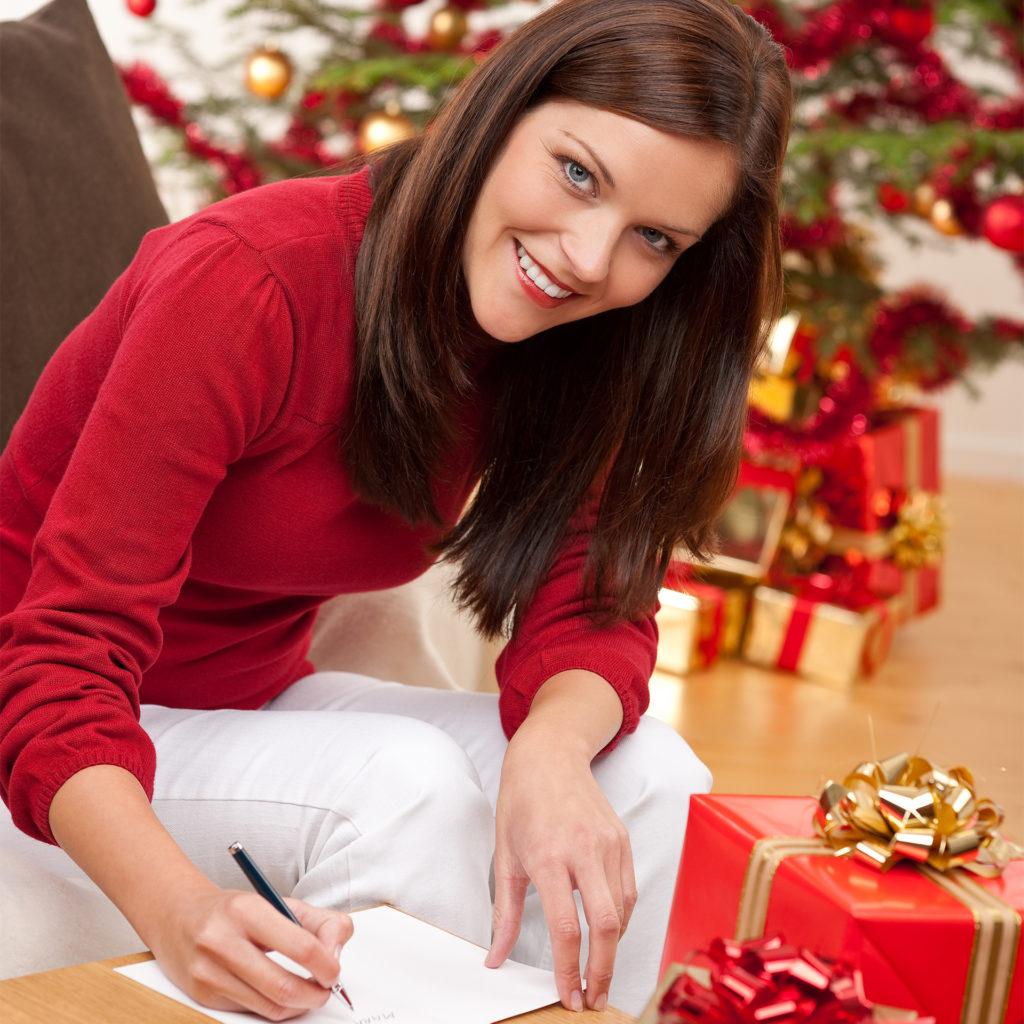 Woman writing cards beside Christmas tree