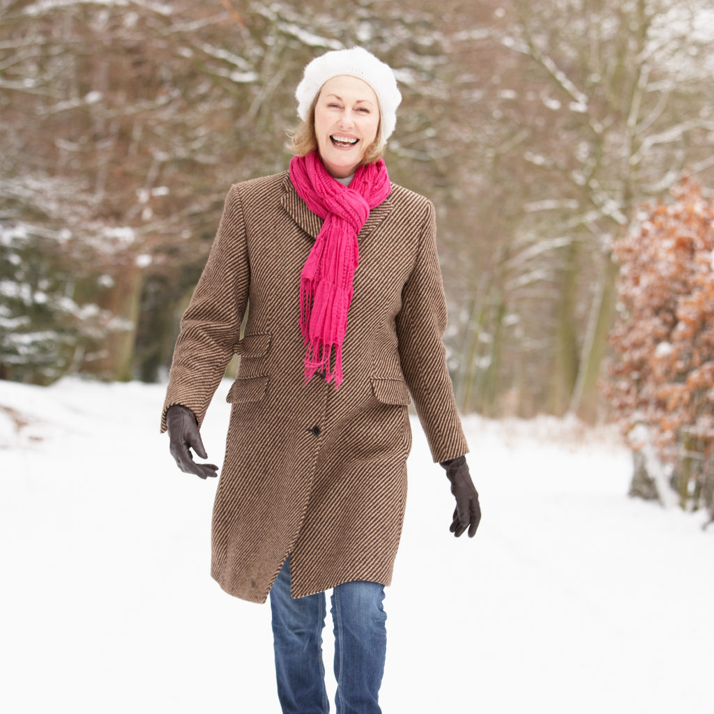 Happy woman in coat, hat and scarf walking through woods in the snow