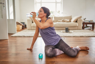 Woman drinking water and exercising in her front room