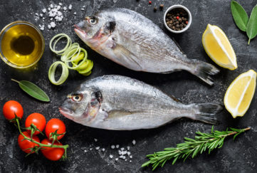 Ingredients laid out on dark granite top- 2 whole sea bream fish, tomatoes, herbs, lemon wedges