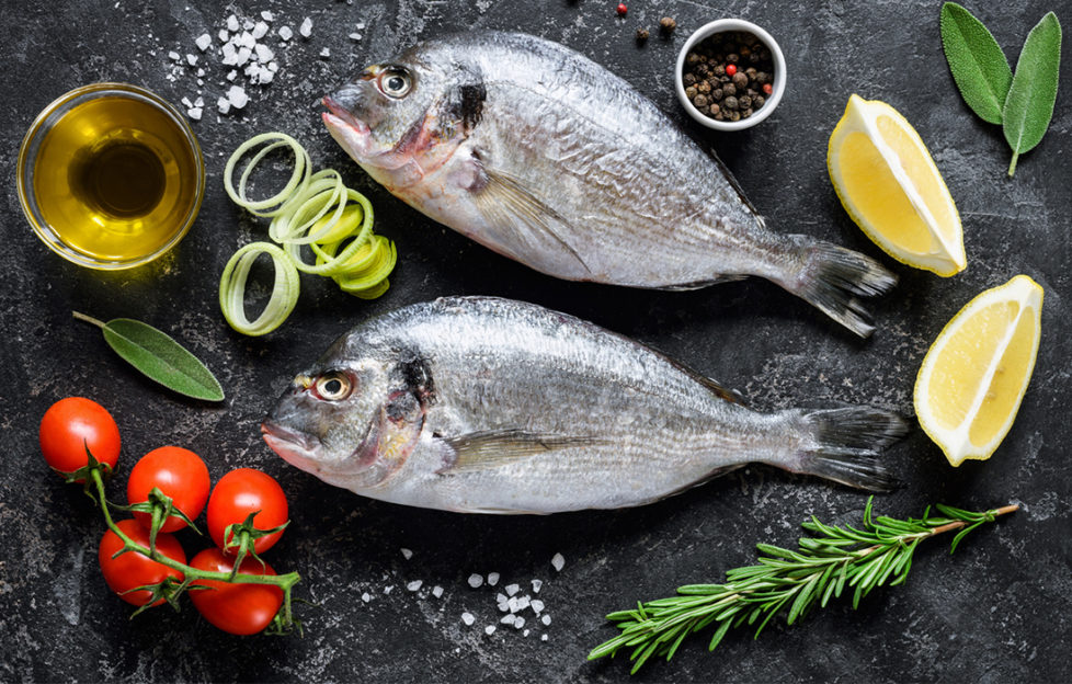 Ingredients laid out on dark granite top- 2 whole sea bream fish, tomatoes, herbs, lemon wedges