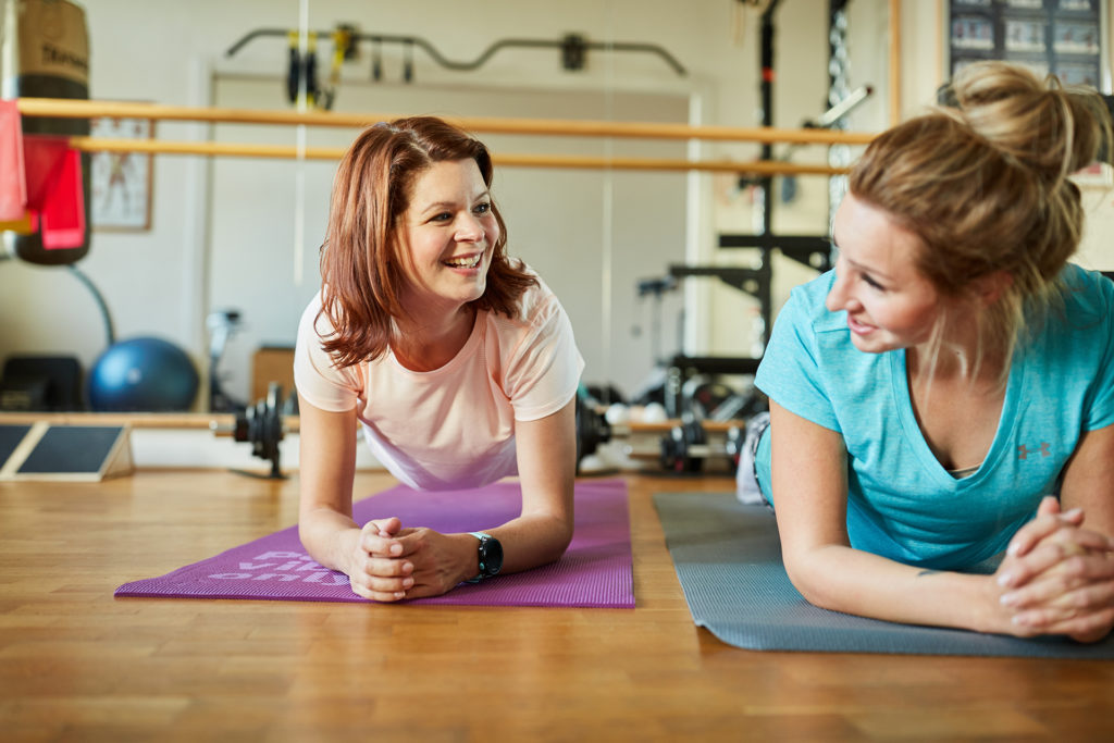2 women lying face down on exercise mats