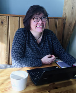 Dark haired woman with glasses, looking up from laptop computer in cafe, smiling