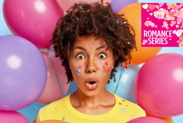 Young mixed race woman looking shocked and scared, surrounded by bright coloured balloons