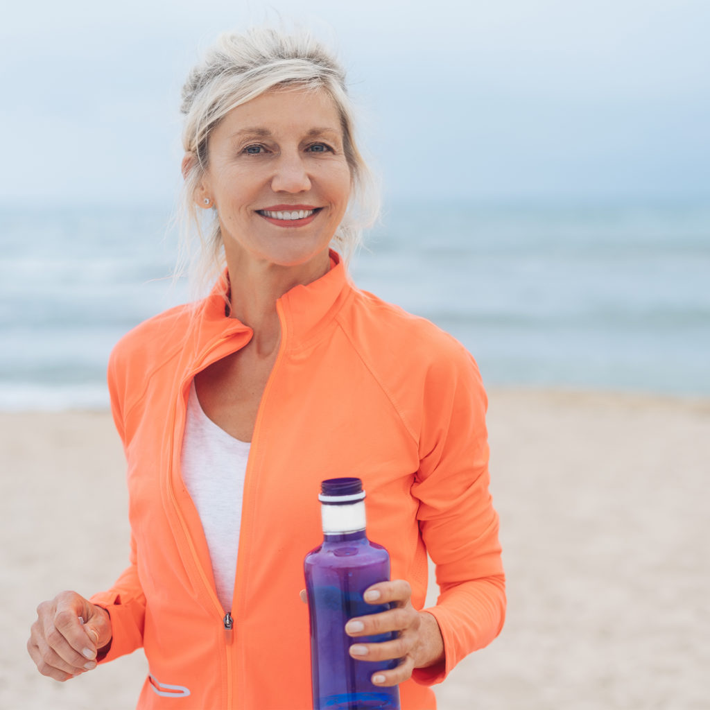 Vivacious fit woman walking on a beach in colorful sportswear carrying water bottle