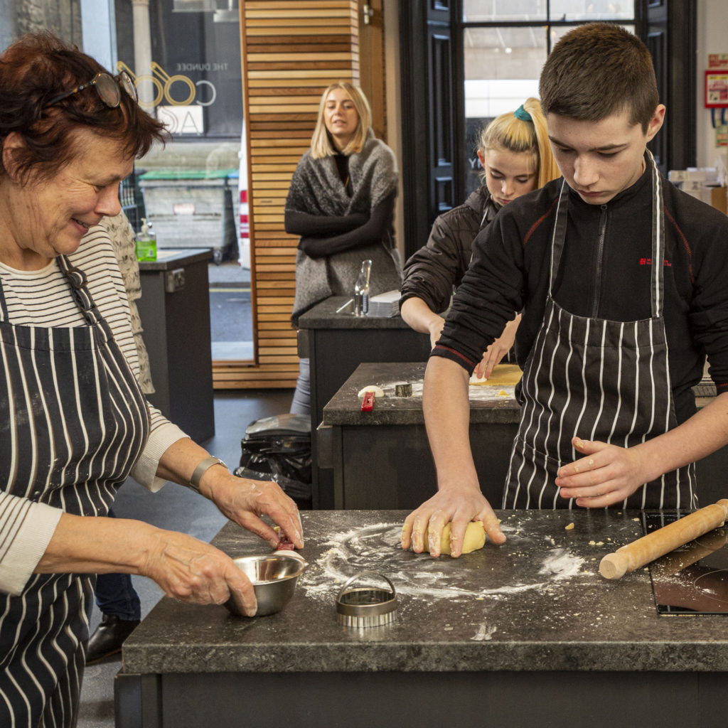 Smiling older woman and teenage boy, both in striped cook's aprons, kneading biscuit dough.