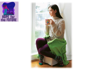 Young woman in thick purple tights sitting on pouffe looking out of the window, holding a mug, looking sad and tense