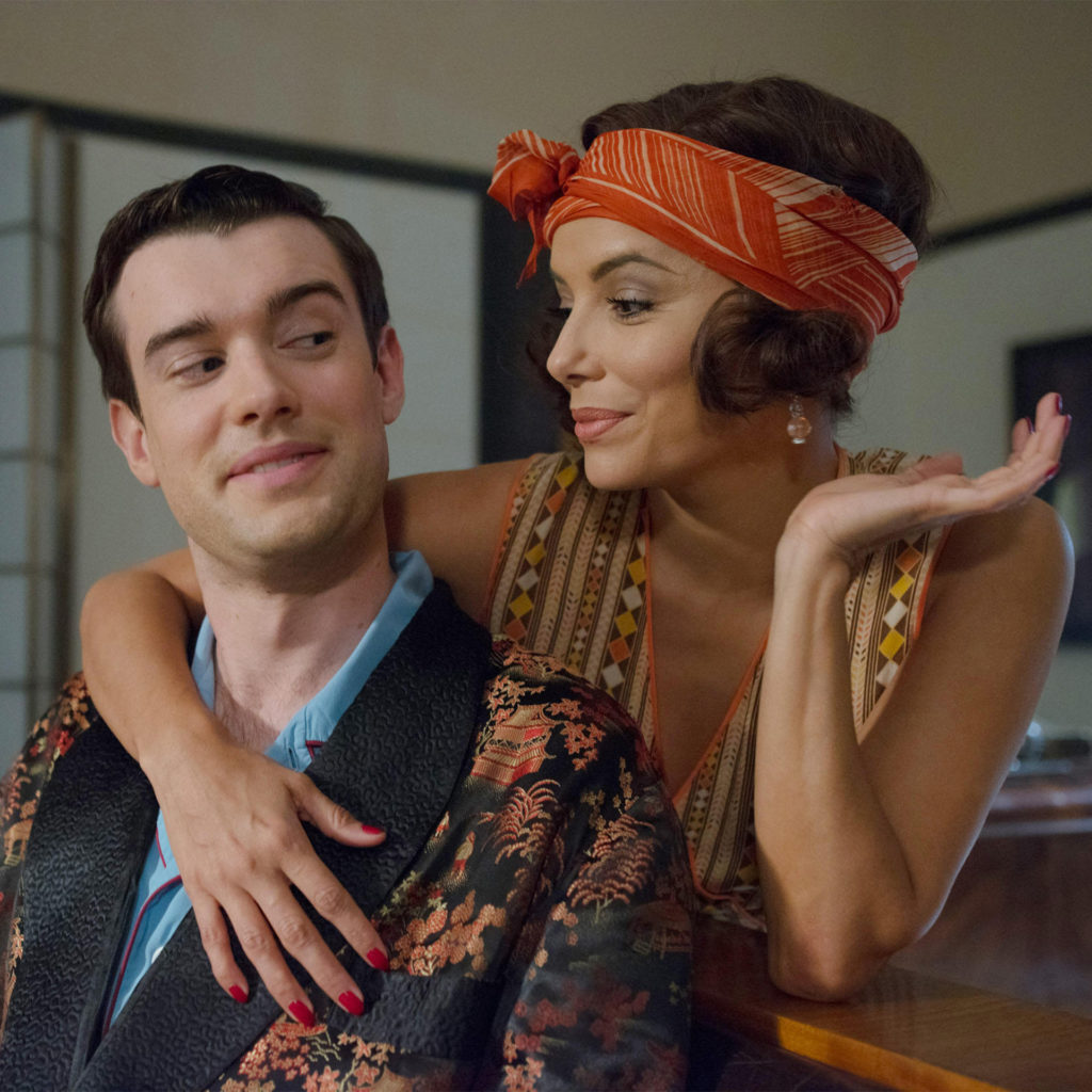 Jack Whitehall looks coyly at Eva Longoria, in glamorous 1920s clothes, as she leans over him flirtatiously