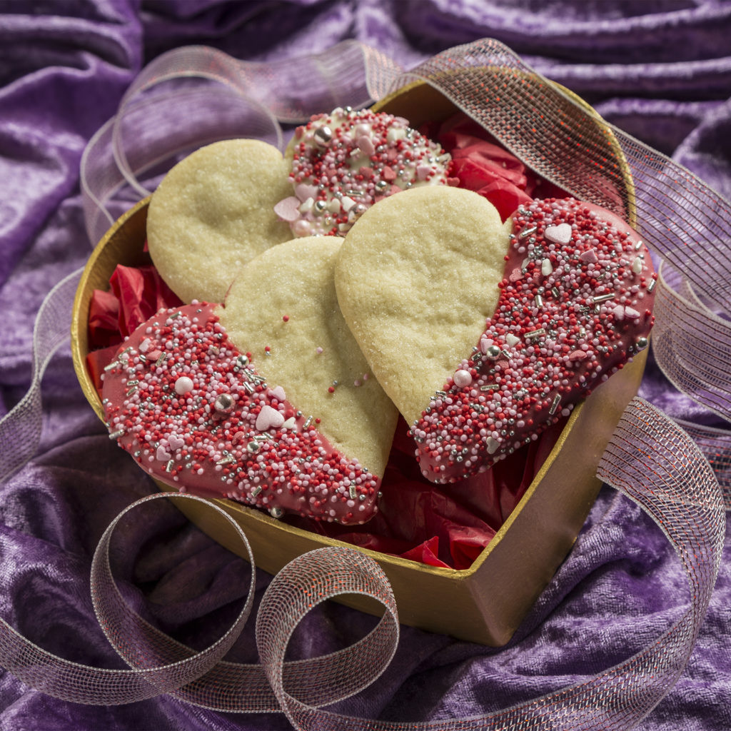 heart shaped box, heart shaped biscuits half covered in sprinkles