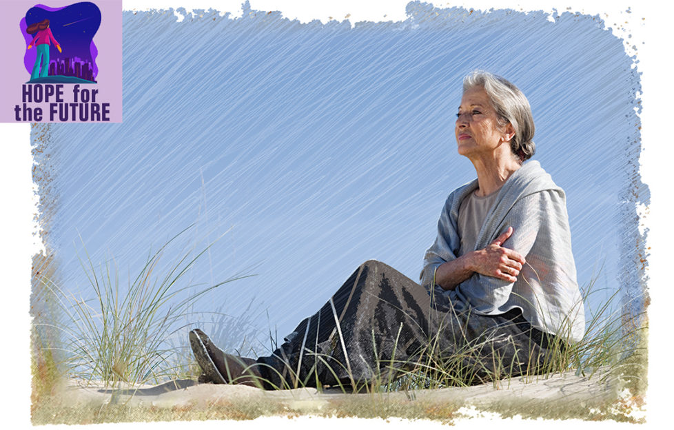 Mature woman sitting on sand dune, looking out to sea, sea grass in foreground