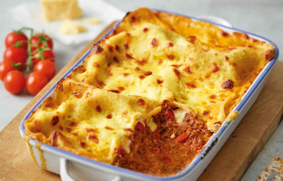 Ovenproof dish filled with golden brown cheese-topped lasagne, one portion scooped out revealing tomatoey mixture