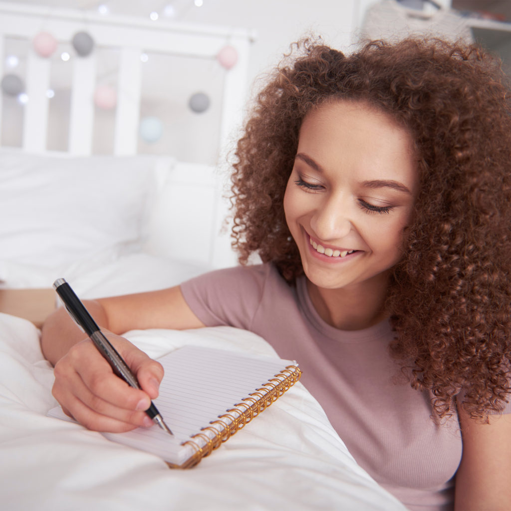 Young woman writing in diary, leaning on end of her bed