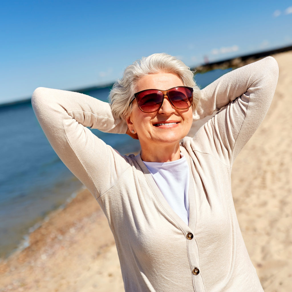 Senior lady in sunglasses and light cardigan on the beach enjoying the sun