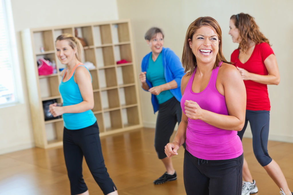 Happy women working out together in fitness exercise class.