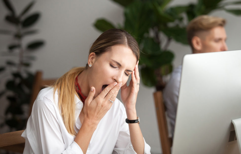 Bored tired businesswoman yawning at workplace feeling lack of sleep