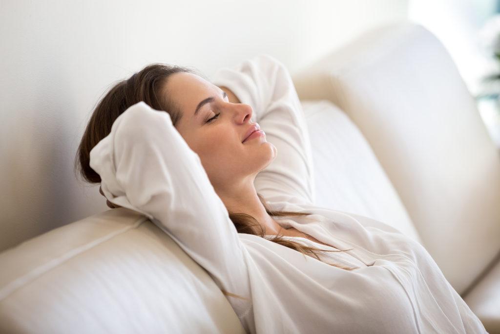 Calm millennial woman relaxing on comfortable sofa breathing fresh air