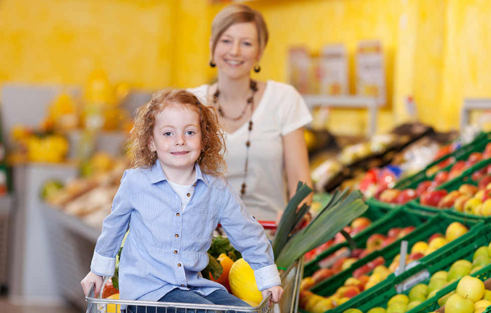 mother in a supermarket pushing a trolley filled with fresh fruit and veg with the daughter riding on the front