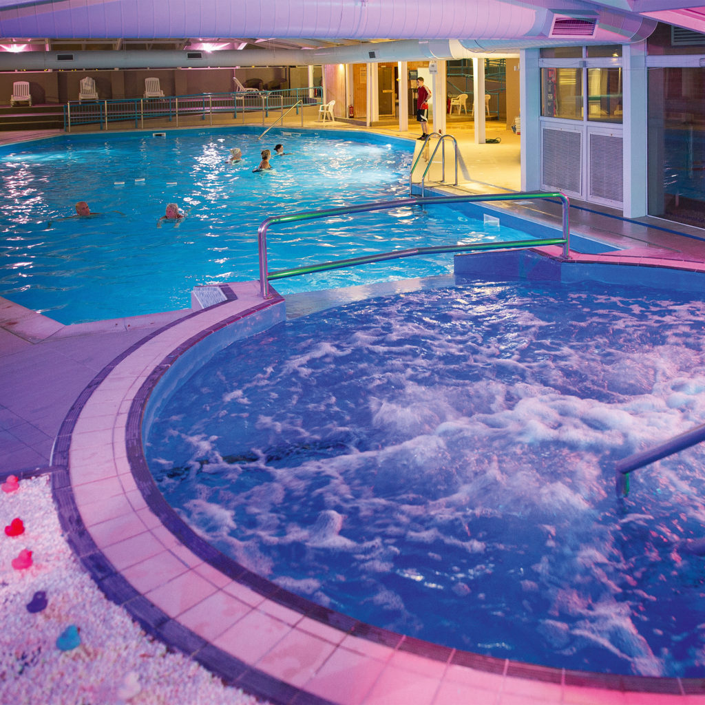 Jacuzzi and indoor swimming pool beyond, soft lighting, few people