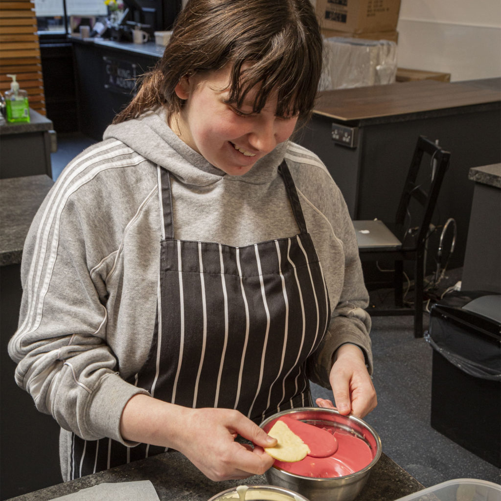 Girl in grey hoodie and cook's apron smiles as she dips biscuit into melted red icing