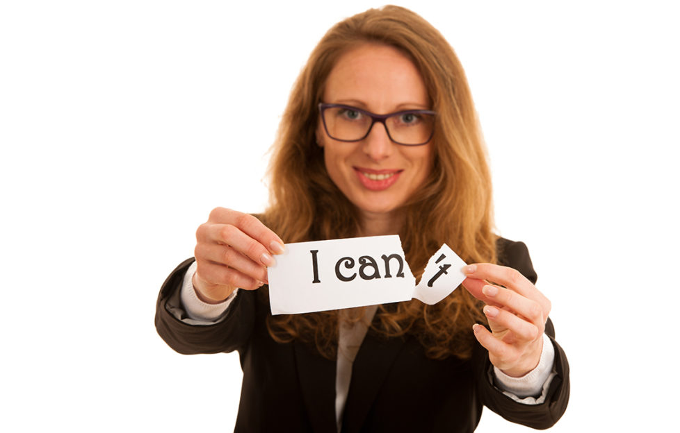 """Keeping new year resolution. Smiling woman holding out paper that says """"I can't"""", she is tearing off the end to leave """"I can"""""""