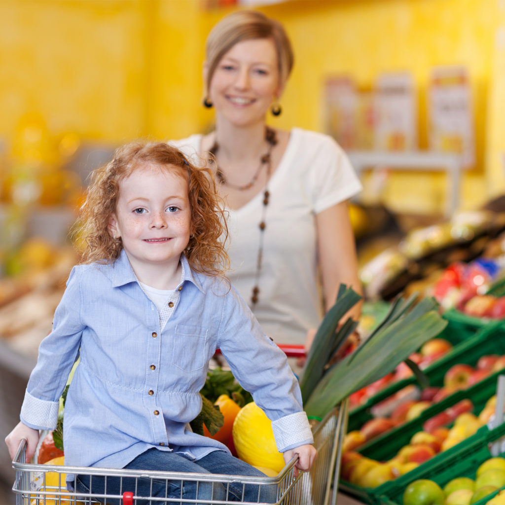 mother in a supermarket pushing a trolley filled with fresh fruit and veg with the daughter riding on the front;
