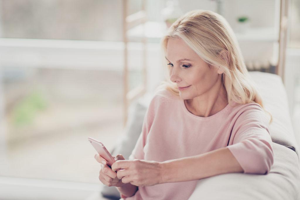 Older blonde woman sitting on settee looking at her smart phone