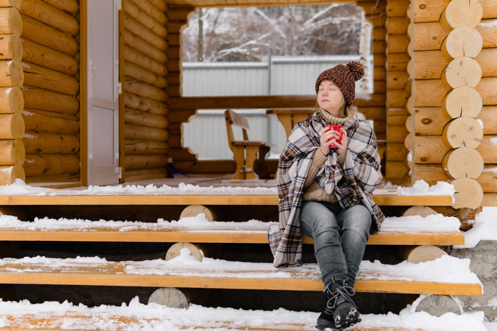 Woman in warm blanket relaxing and drinking morning coffee on the steps log cabin in winter.