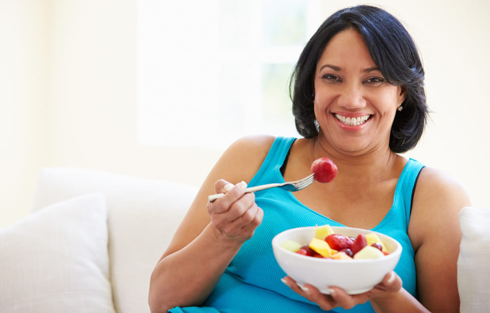 Overweight Woman Sitting On Sofa Eating Bowl Of Fresh Fruit;