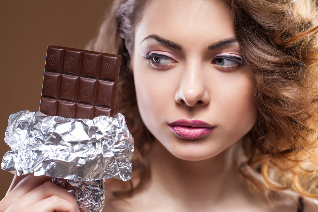 Woman looking sideways at large bar of chocolate