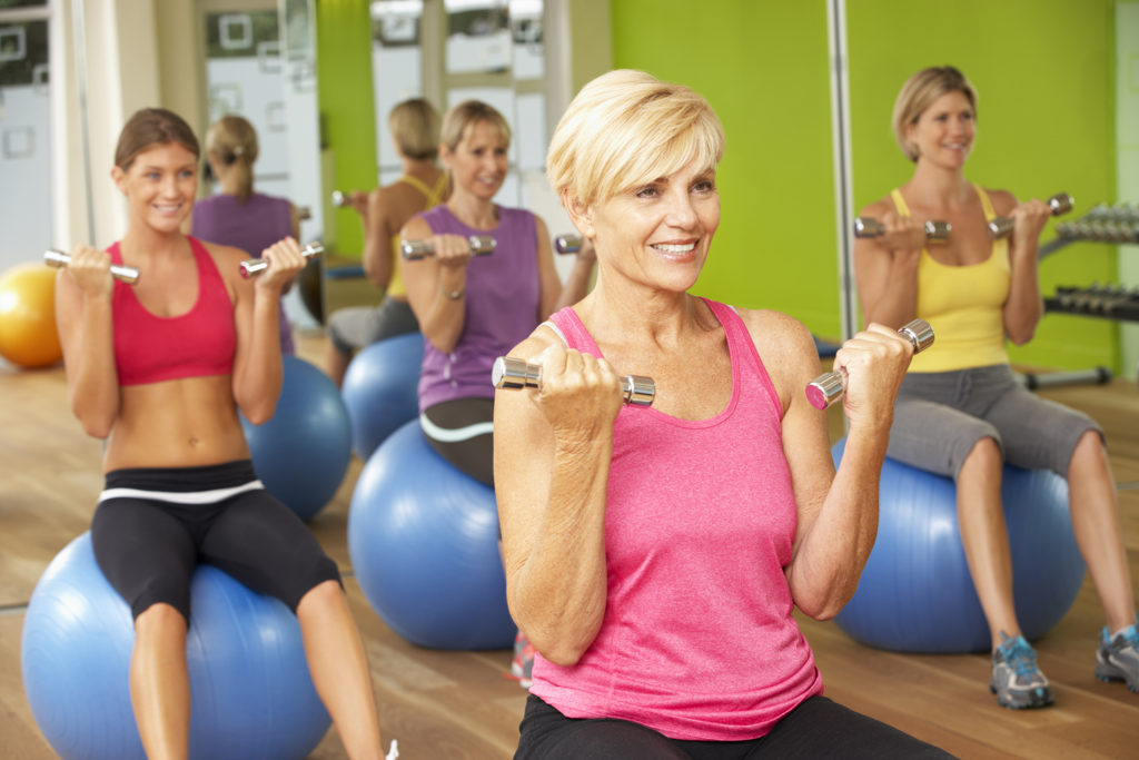 Women Taking Part In Gym Fitness Class;