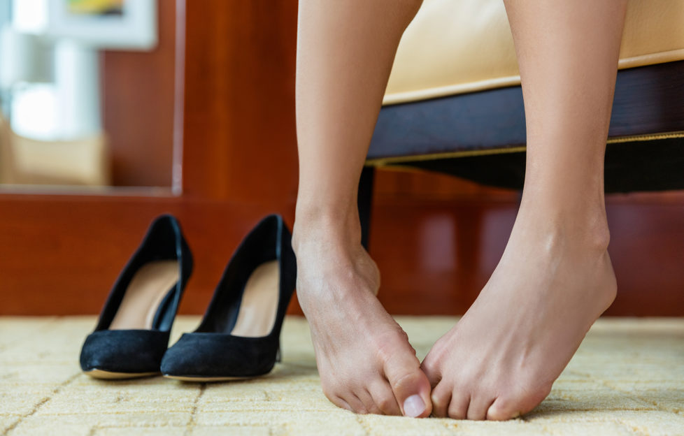 High heels shoe feet pain. Closeup of woman barefoot with painful toes has removed her formal stilettos at work